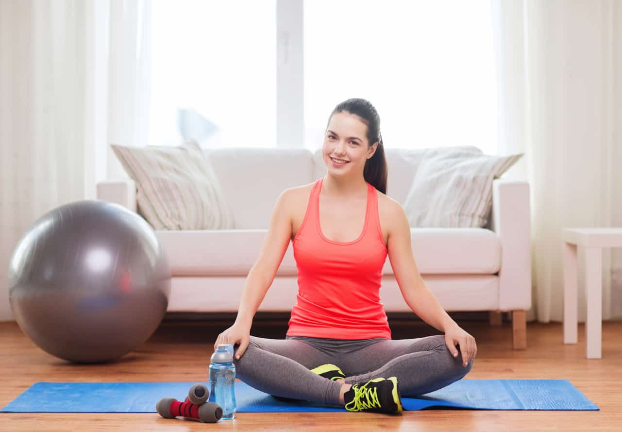 Smiling girl sitting on mat with sports equipment